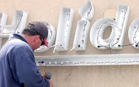 Picture of man retrofitting sign